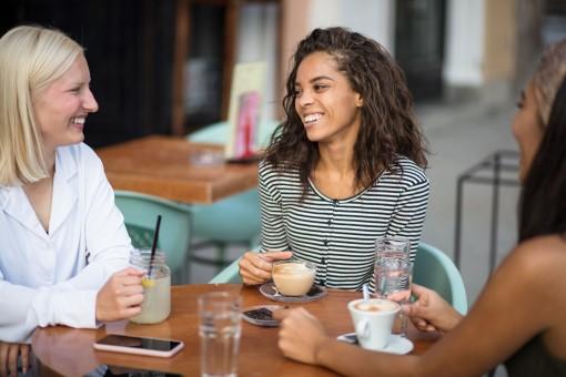 Eine drei Frauen sitzen in einem Cafe und unterhalten sich. Sie lachen ausgiebig.