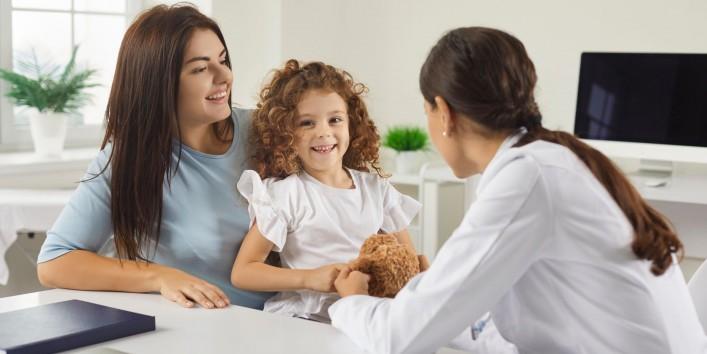 Eine Mutter sitzt mit ihrer Tochter bei einer Ärztin und lässt sich beraten. Alle lächeln.