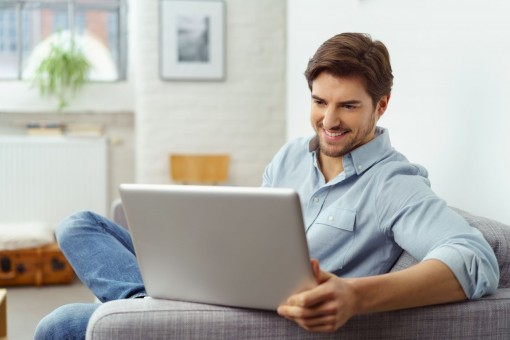 Ein etwa 35 jähriger Mann sitzt auf einem Sofa. Auf der Armlehne stützt er seinen Laptop. Er schaut auf den Laptop und lächelt.