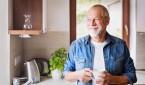 Älterer Mann steht in der Küche und schaut aus dem Fenster
