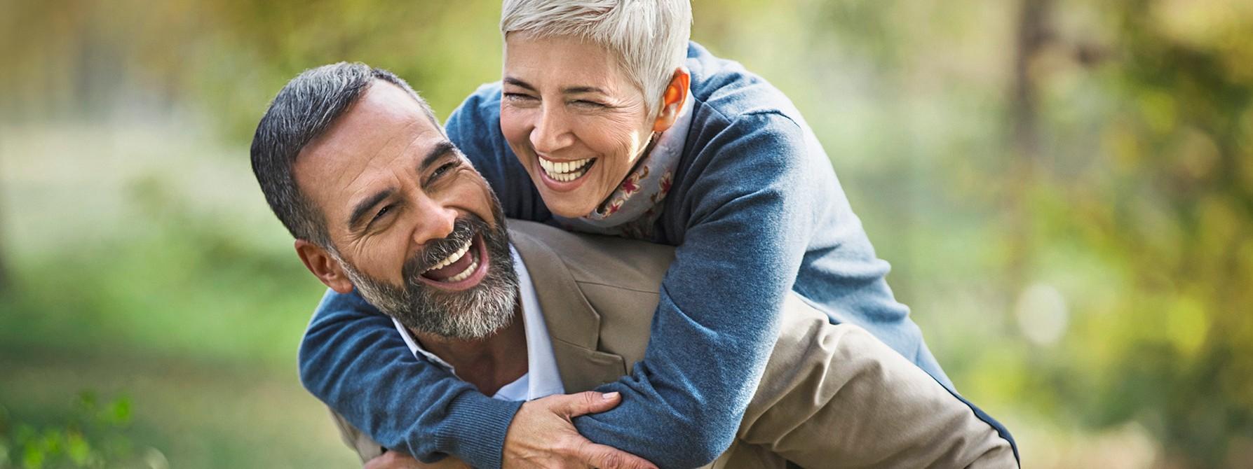 Älterer Mann trägt fröhlich lachend eine ältere, ebenso fröhlich lachende Frau Huckepack.