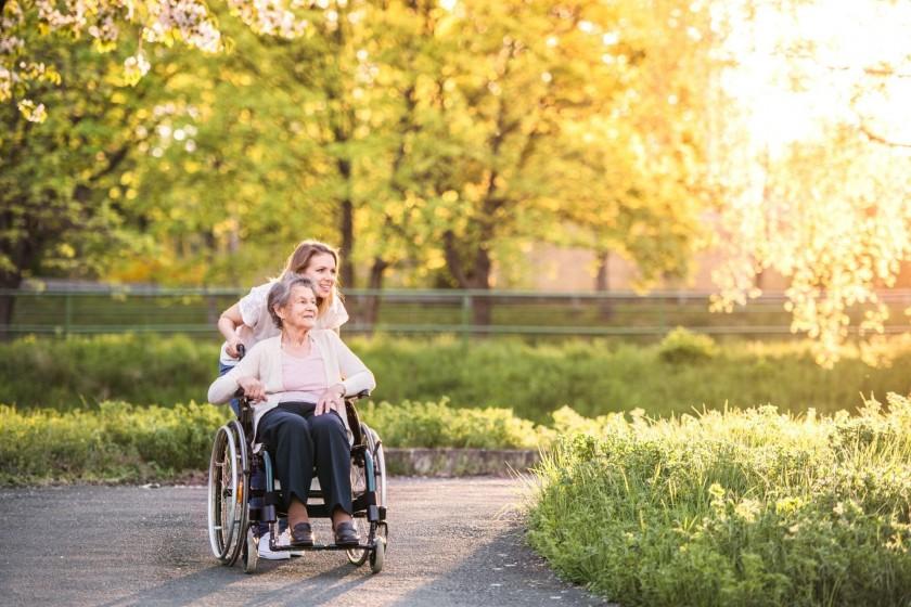 Eine Seniorin wird von einer jungen Frau im Rollstuhl durch die Natur gefahren. Beide schauen in eine Richtung und lächeln.