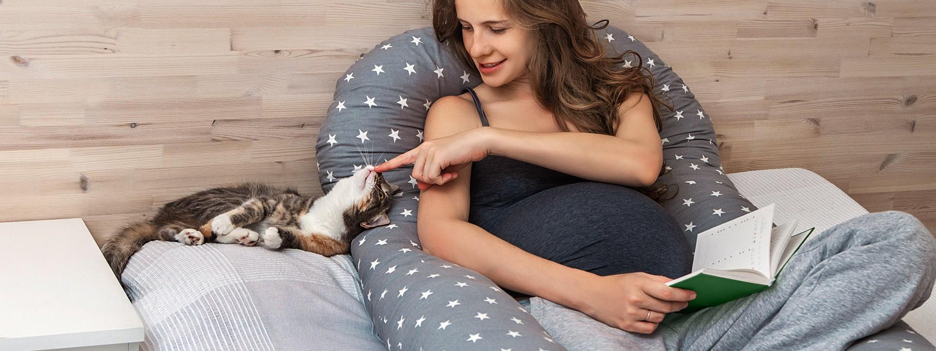 Schwangere Frau liegt auf dem Bett mit Katze