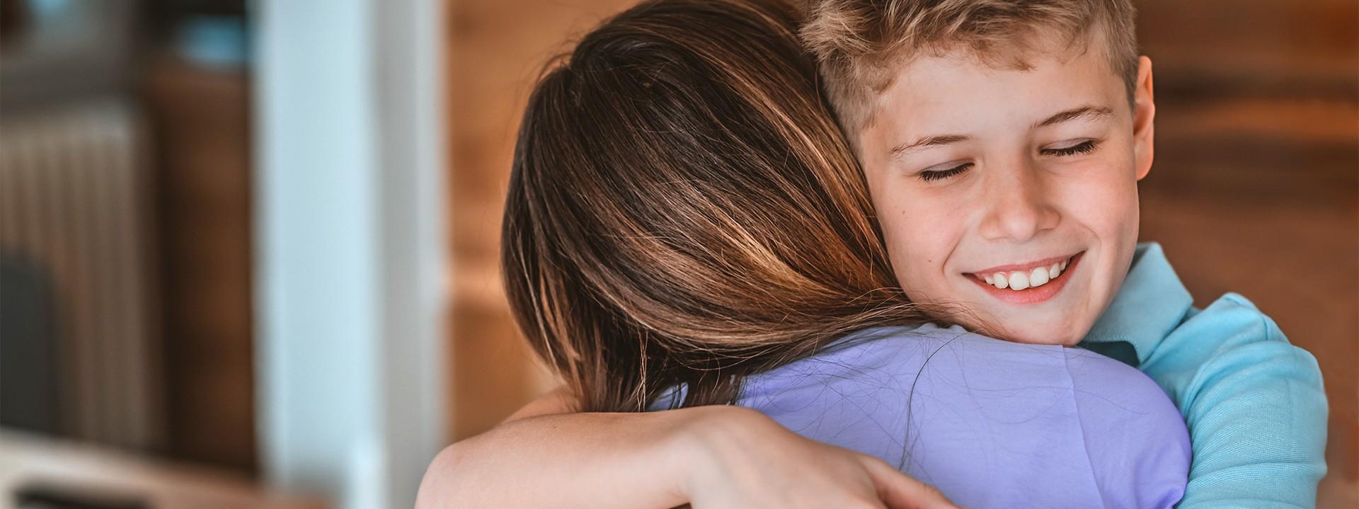 Ein Junge umarmt eine Frau und lächelt dabei.