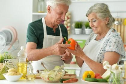Ein Seniorenpaar steht gemeinsam in der Küche und kocht. Die Frau hält eine Paprika in der Hand. Beide lächeln.