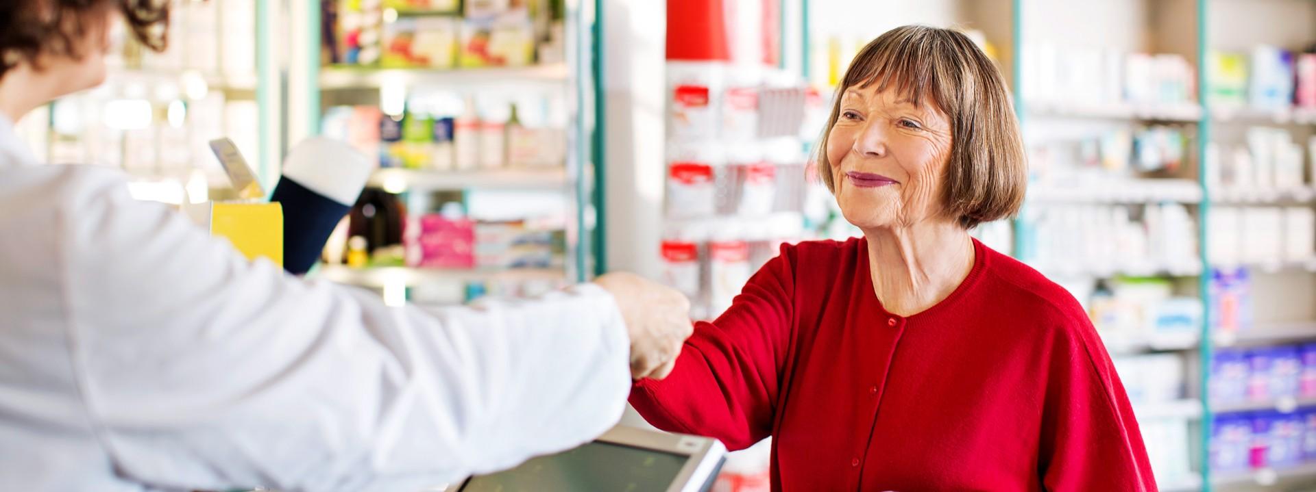 Eine Seniorin in roten Pullover steht in einer Apotheke und lässt sich von einer Apothekerin beraten. Sie lächelt.