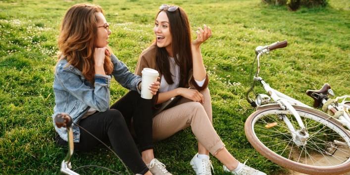 Zwei etwa 20 jährige Frauen sitzen auf einem Rasen und unterhalten sich freudig. Vor ihnen liegen ihre Fahrräder.