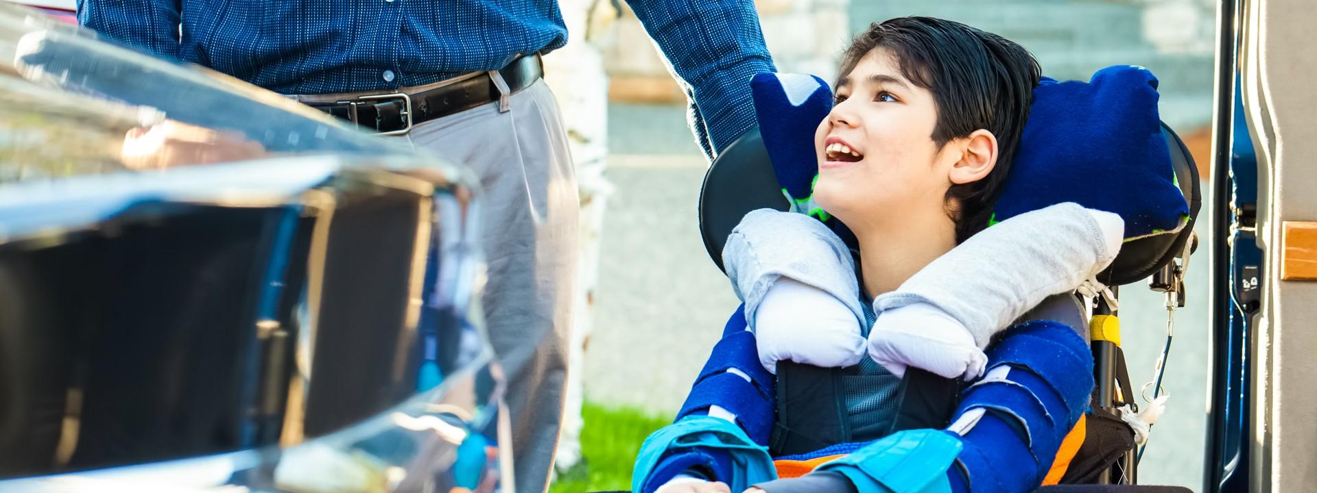 Ein Kind sitzt im Rollstuhl und wird von einem Erwachsenem geschoben.