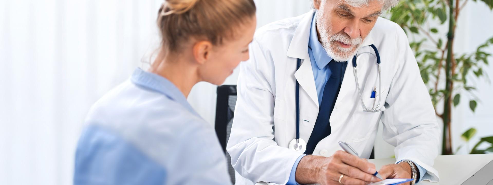 Ein etwas 60 jähriger Arzt sitzt einer etwas 25 jährigen Frau an einem tisch gegenüber. Er berät sie und hat ein Klemmbrett in der Hand.