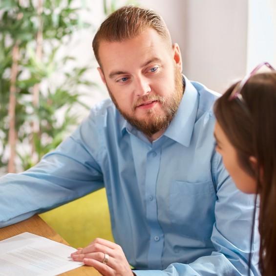 Ein circa 40-jähriger Praxis-Begleiter erklärt einer Auszubildenden einen Sachverhalt anhand eines Dokuments. Er sieht sie dabei an, während sie aufmerksam den Ausführungen folgt.