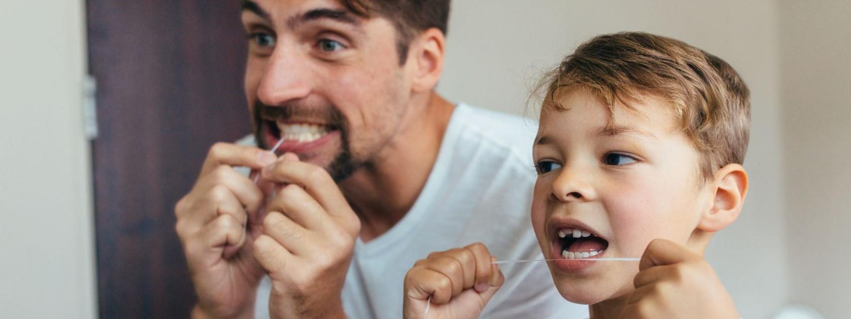 Ein etwa 6-jähriger Junge steht mit seinem Vater im Badezimmer. Sie pflegen mit Zahnseide ihre Zähne.