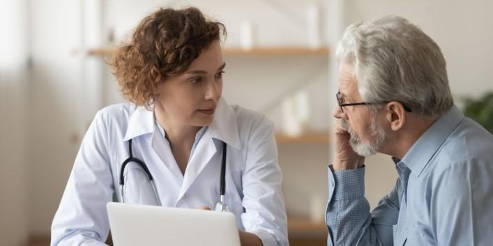 Ein circa 60-jähriger Patient spricht mit seiner circa 40-jährigen Ärztin.