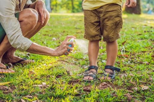 Kinderbeine werden von einer Person mit Anti-Mücken-Spray eingesprüht.