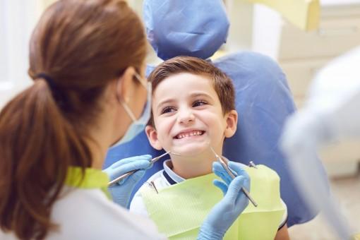 Ein etwa 6 jähriger Junge sitzt auf einem Behandlungsstuhl beim Zahnarzt. Er läcehlt die Zahnärztin an während sie ihn untersucht.