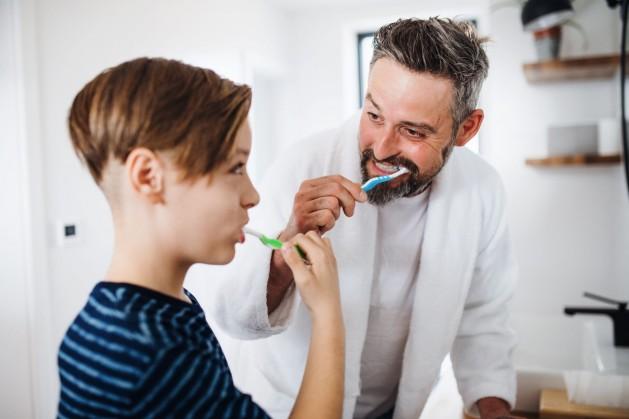 Ein Vater putzt mit seinem etwa 10 jährigen Sohn gemeinsam die Zähne.