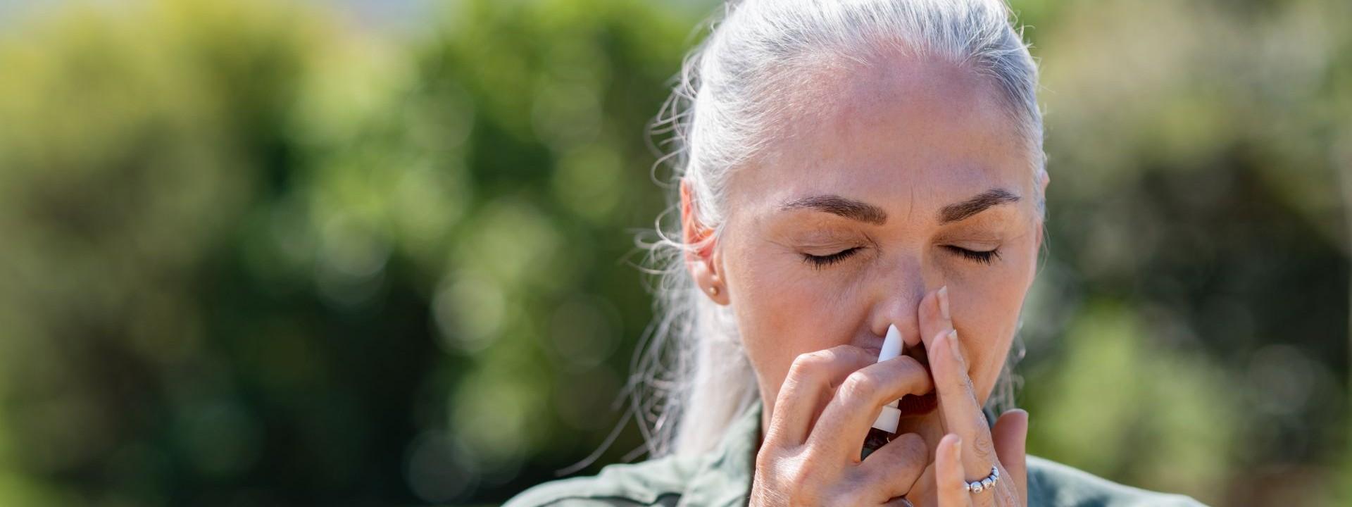 Eine etwa 50 jährige Frau steht in der Natur und hat die Augen geschlossen. Sie hat beide Hände im Gesicht und führt sich ein Nasenspray in die Nase ein.
