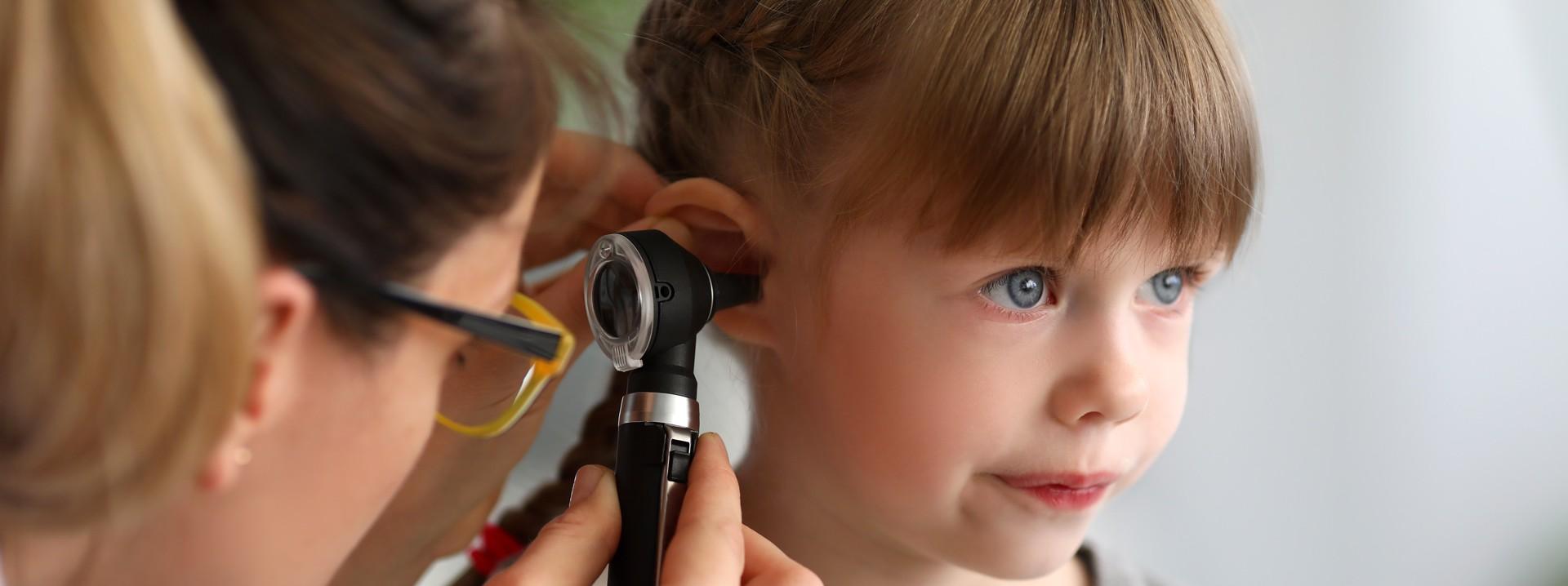 Arzt schaut Mädchen ins Ohr