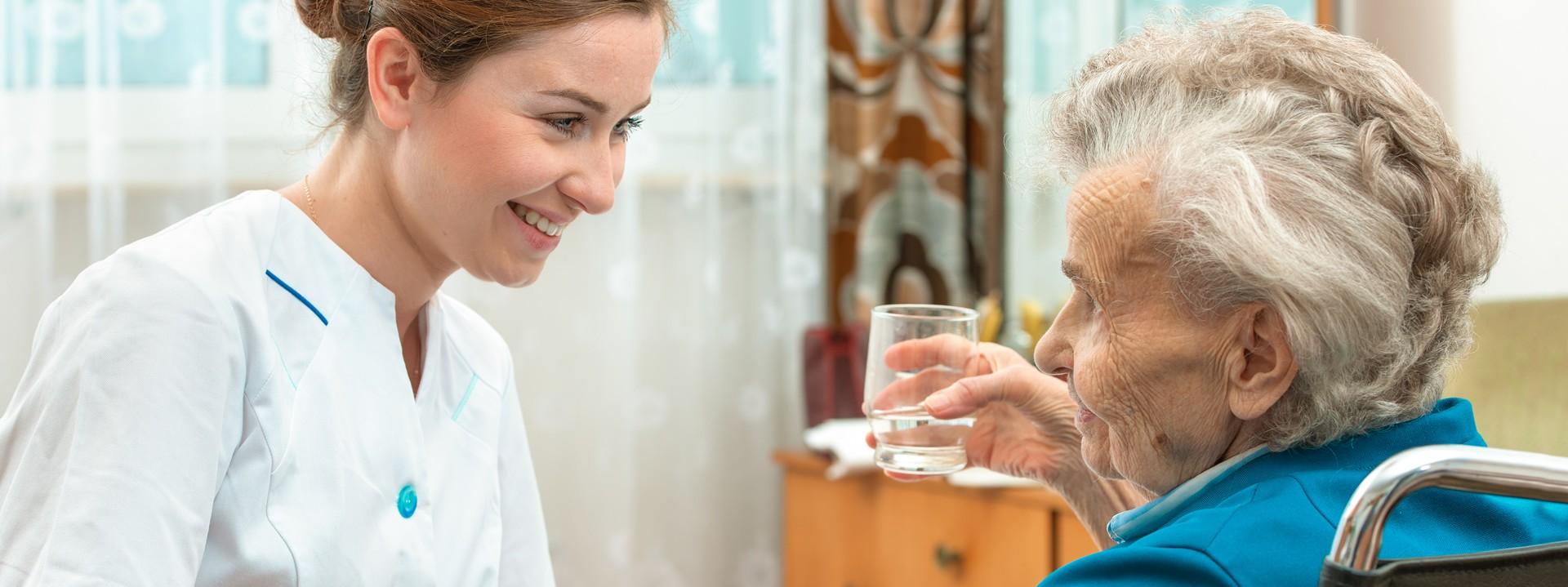 Pflegerin spricht mit Seniorin