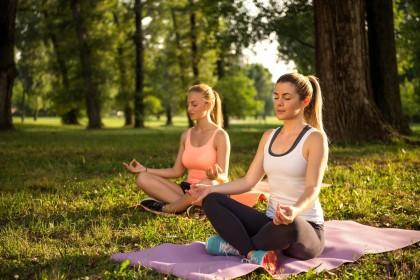 zwei Frauen machen Yoga im Park