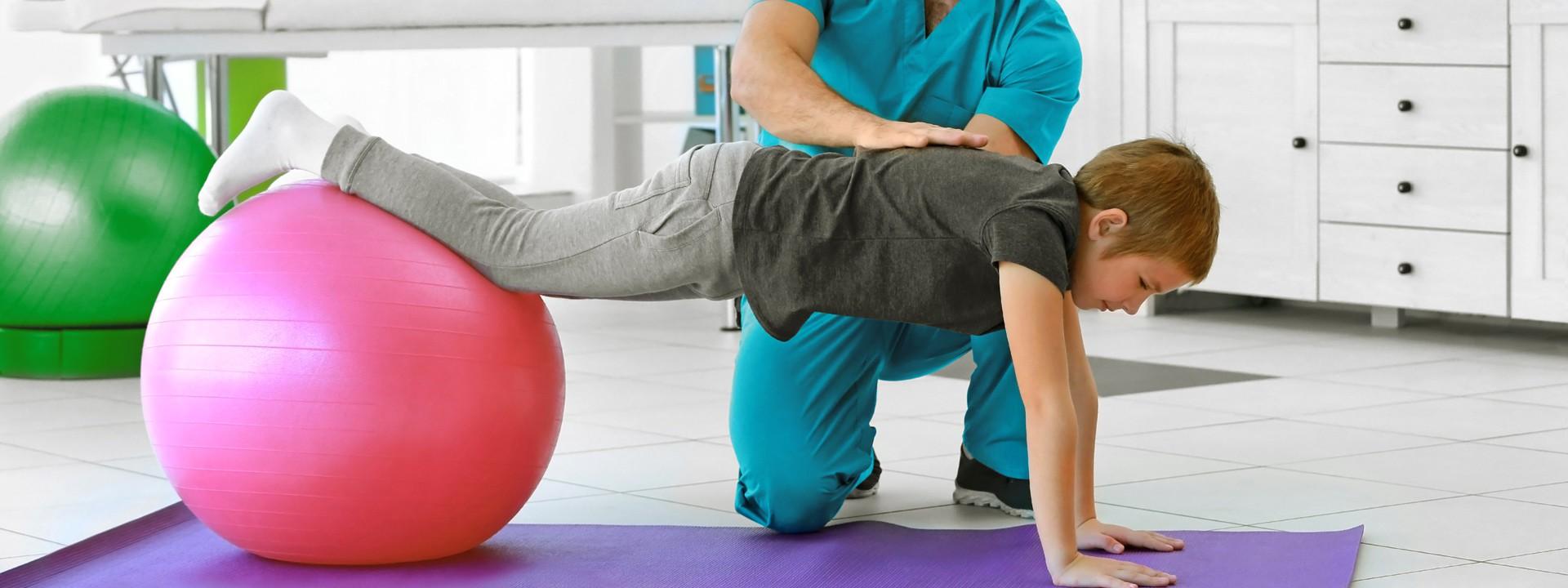 Ein Junge turnt mit einem rosa Gymnastikball und wird von einem Therapeuten unterstützt.