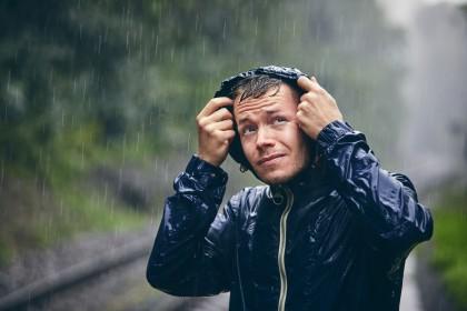 Ein etwa 30 jähriger Mann steht in der Natur im strömenden Regen. Er trägt eine Regenjacke und hat die Kapuze über den Kopf gezogen.