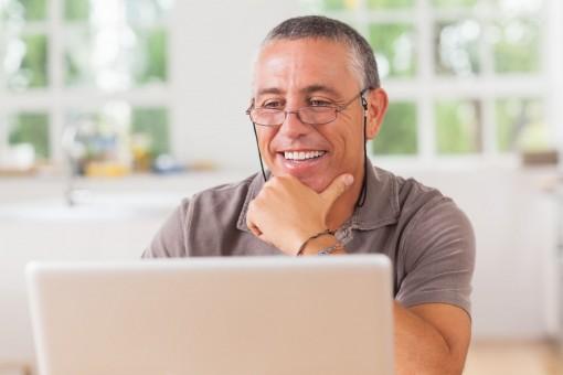 Ein etwa 50 jähriger Mann sitzt interessiert vor seinem Laptop und hat seine linke Hand an das Kinn gelegt. Dabei lächelt er.
