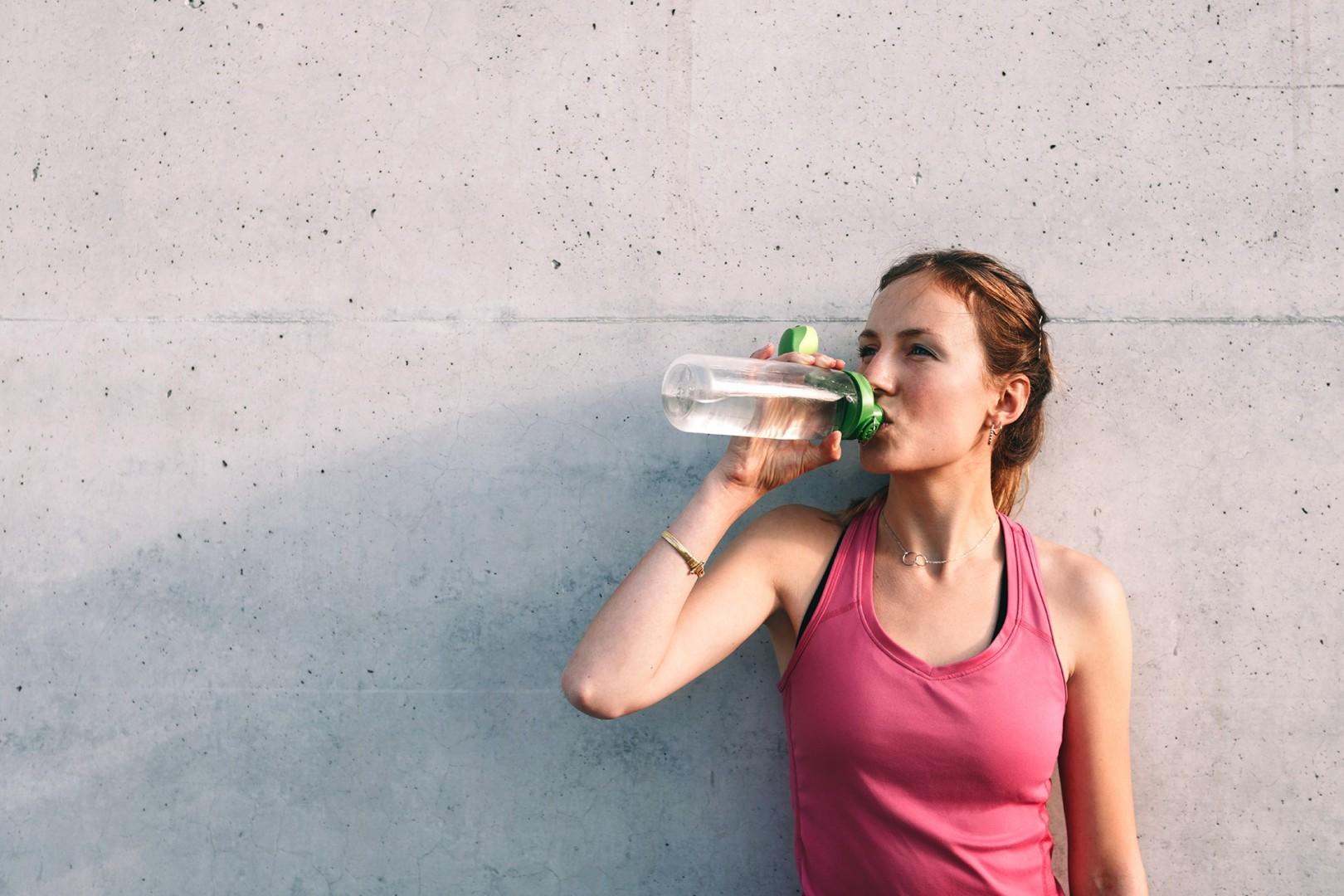 Sportlerin trinkt aus einer Flasche