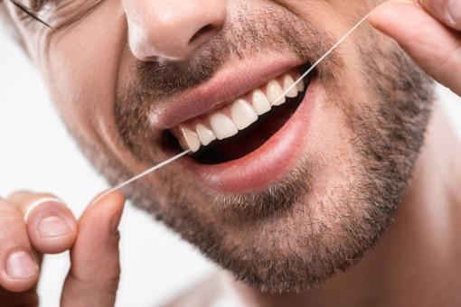 Ein Mann reinigt seine Zähne mit Zahnseide.