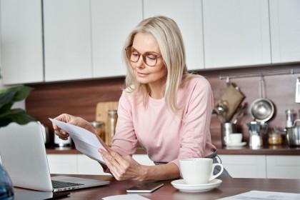 Eine etwa 55 jährige Frau steht in der Küche und liest sich ein Blatt Papier durch. Vor ihr steht ein Laptop und neben ihr eine Tasse.