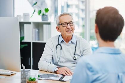 Ein etwa 60 jähriger Arzt sitzt an einem Schreibtisch und berät einen etwas 30 jährigen Patienten.