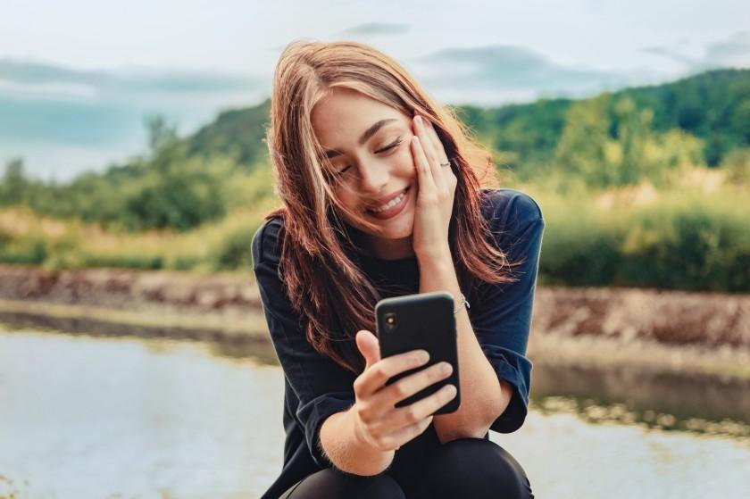 Eine etwa 30-jährige Frau sitzt an einem Fluss und schaut auf ihr Handy.