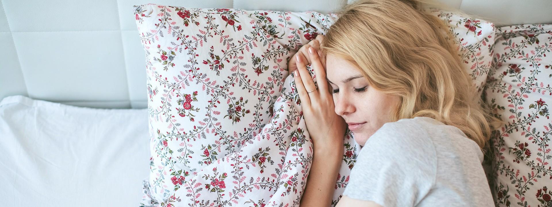 Eine blonde Frau liegt in einem weißen Bett und schläft.