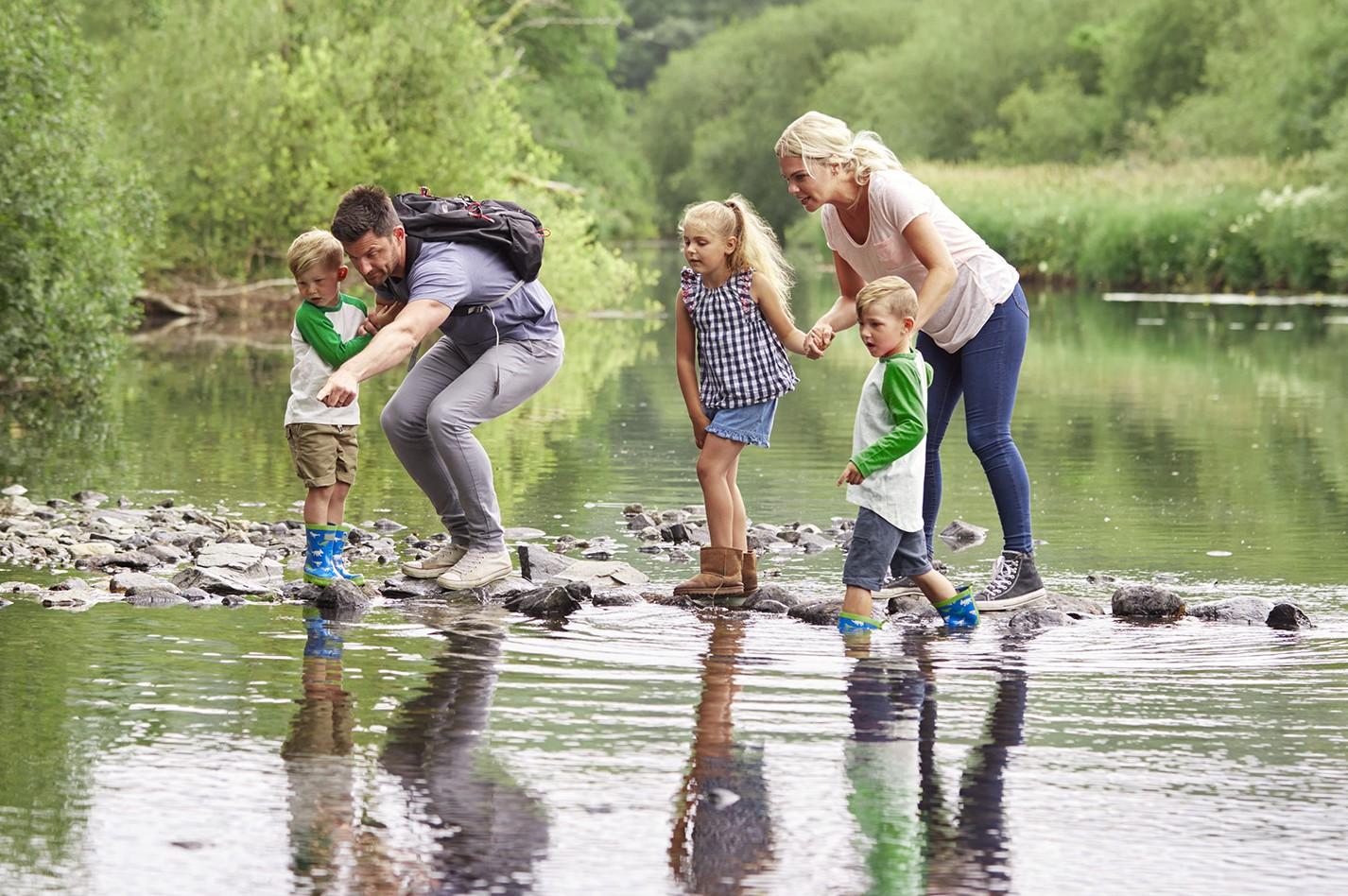 Vater, Mutter und Kinder beim Wandern über einen See.