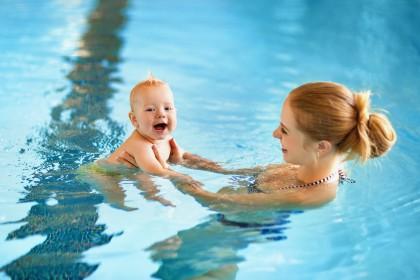 Mutter mit Baby im Wasser eines Schwimmbades.