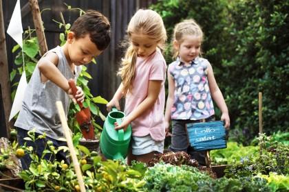 Kinder bei der Gartenarbeit an einem Hochbeet.
