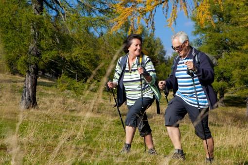 Ein Seniorenpaar betreibt Nordic-Walking in der Natur. Beide lächeln ausgelassen.