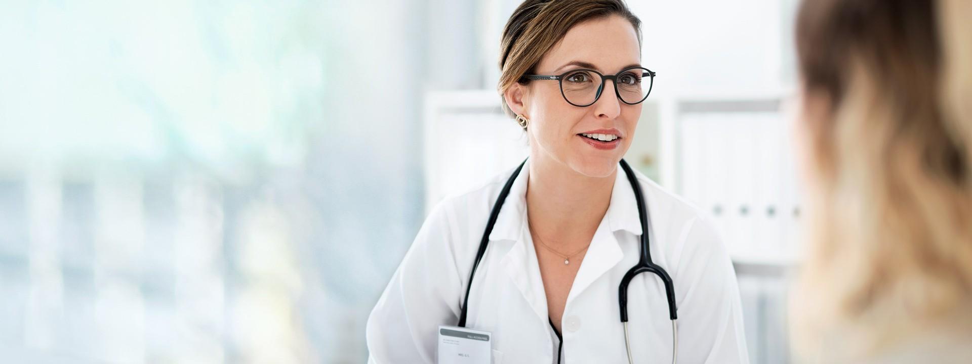 Eine Ärztin mit weißem Kittel und Stethoskop um dem Hals berät in einer Praxis eine junge Frau.