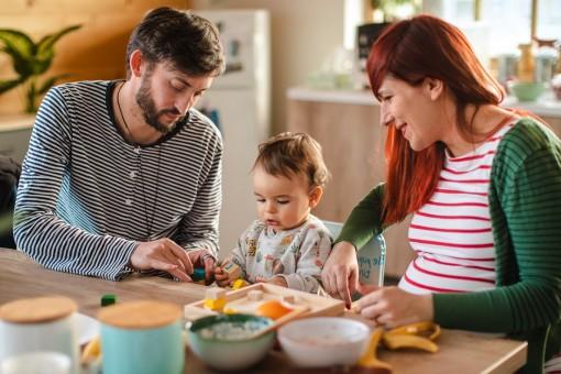 Eine etwa 30-jährige Schwangere frühstückt zusammen mit ihrem Mann und ihrem etwa 1-jährigen Kind.