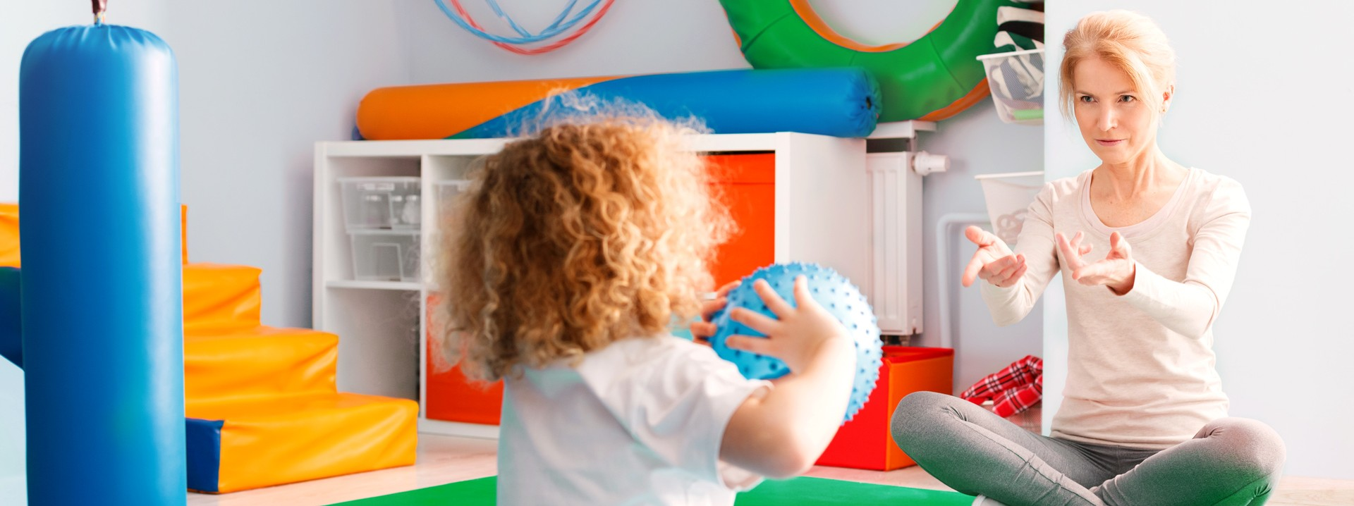 Kind und Ergotherapeutin werfen sich einen Ball zu.