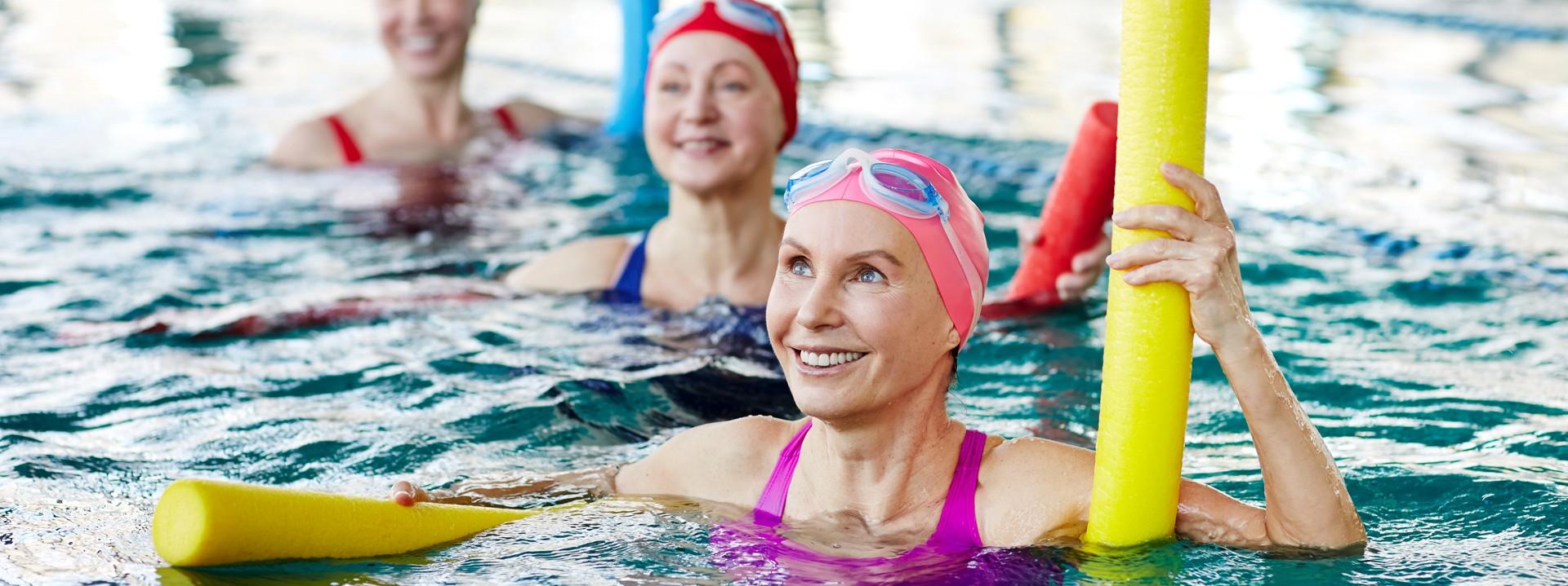 Drei Frauen befinden sich in einer Schwimmhalle im Wasser und machen Wassergymnastik mit bunten Badenudeln.