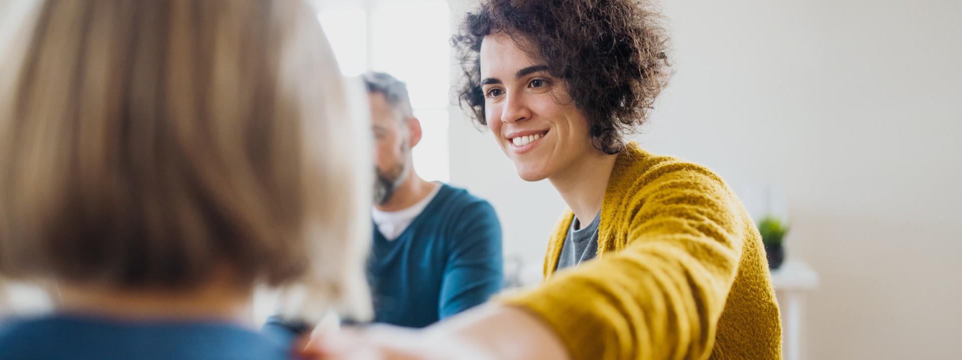 Zwei Frauen sitzen sich gegenüber und lächeln sich an. Eine Frau legt der anderen Frau ihre linke Hand auf die Schulter.sch und unterhalten sich. Die rechte Frau hält in der rechten Hand einen Stift und macht Notizen.