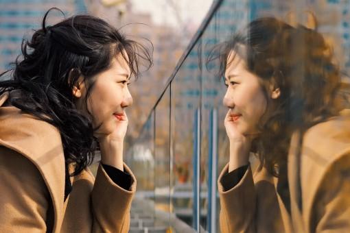 junge Frau betrachtet ihr Spiegelbild und lächelt