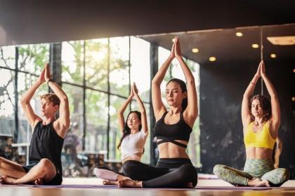 Drei Frauen und ein Mann machen in einem Sportraum Yoga. Alle sitzen im Schneidersitz auf Yogamatten. Die Augen sind geschlossen und die Hände geschlossen über den Kopf gestreckt.