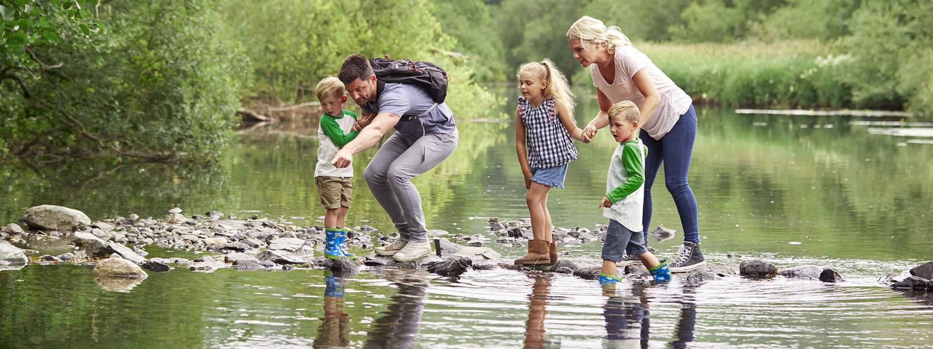 Familie überquert einen Fluss