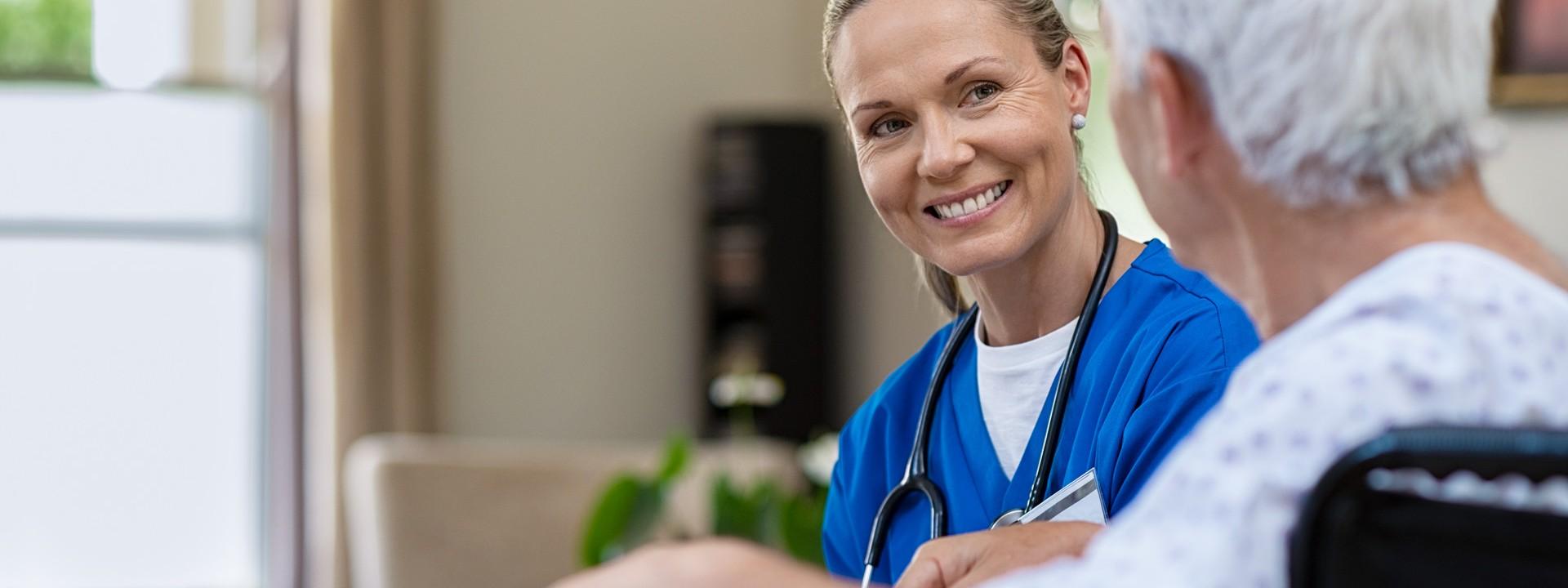 Eine blonde Frau mit blauem Kittel und Stethoskop um den Hals sitzt einer Seniorin gegenüber. Beide lächeln sich an.