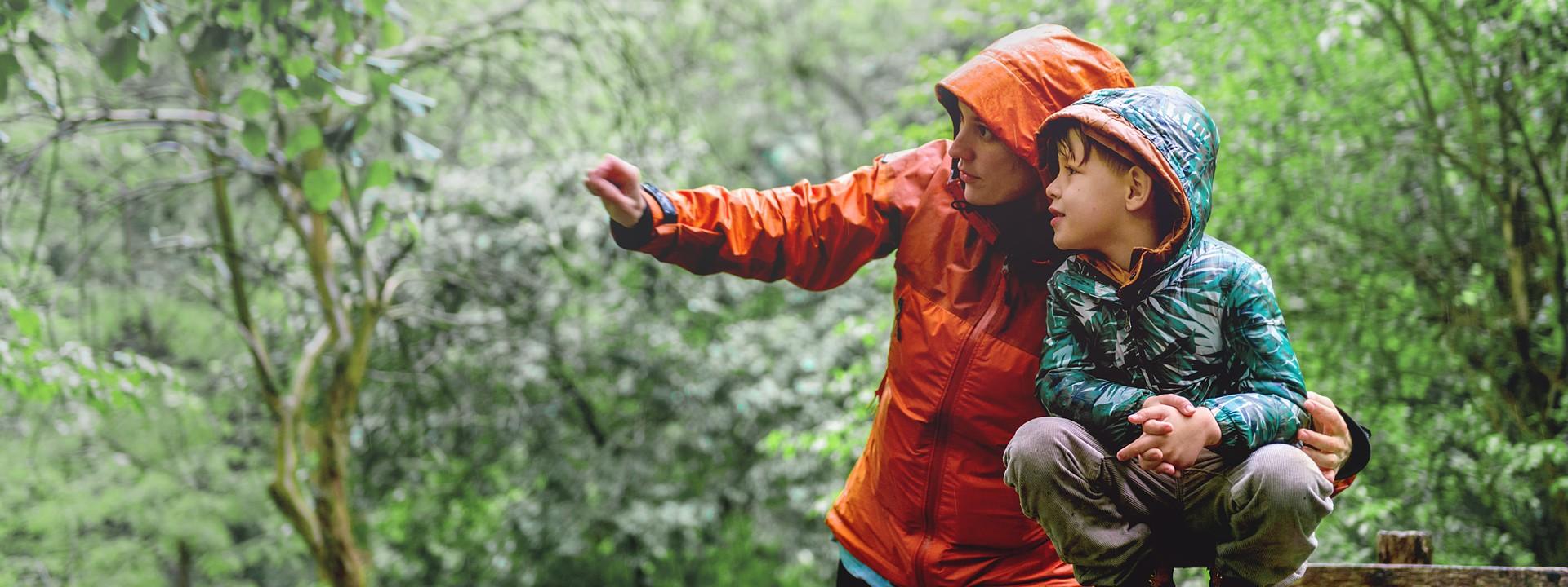 Eine etwa 40-jährige Mutter zeigt ihrem etwa 6-jährigen Sohn etwas mit Regenkleidung im Wald.