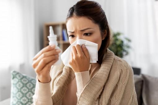 Eine etwa 30 jährige Frau sitzt mit einer Decke über den Schultern auf einem Sofa in einem Wohnzimmer. Die Frau schaut zweifelnd auf ein Nasensprays und schnäuzt sich parallel die Nase.