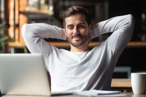 Ein etwa 30-jähriger Mann sitzt am Laptop und lächelt.
