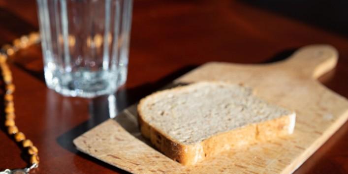 Auf einem Tisch stehen ein Glas und ein Brettchen mit einer Scheibe Brot. Daneben liegt ein Kruzifix.
