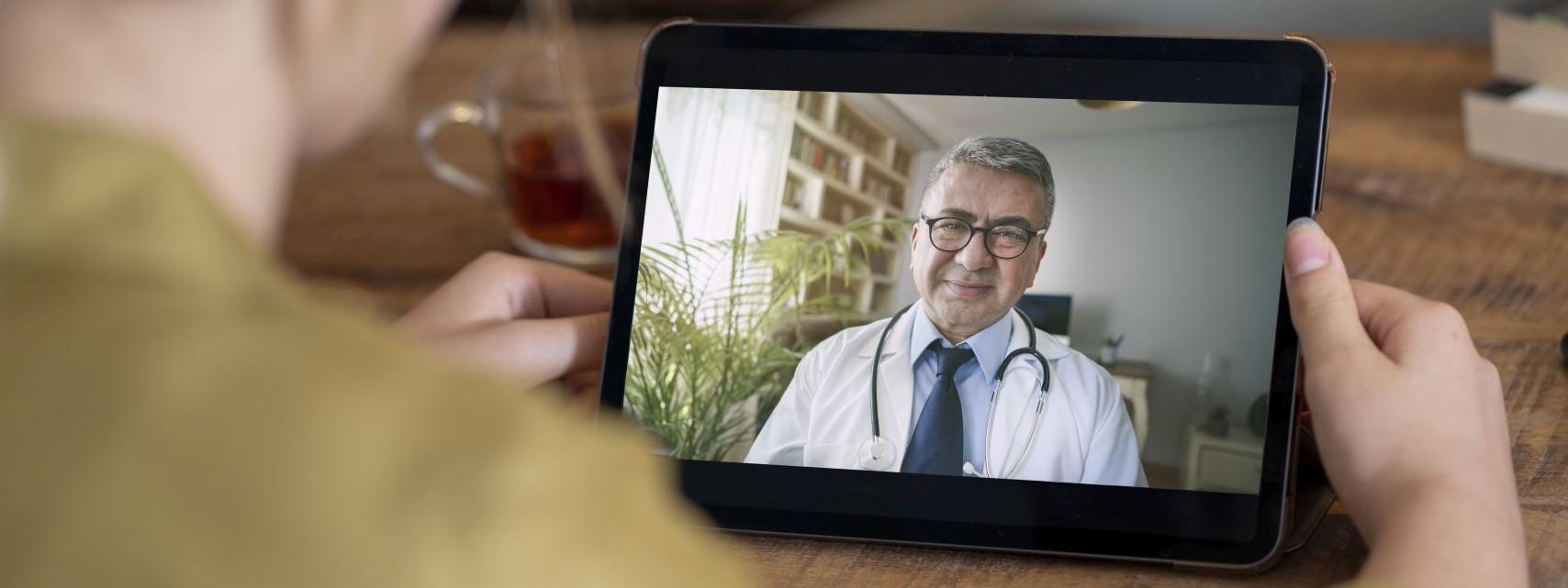 Eine Frau hält ein Tablet in der Hand. Auf dem Bildschirm ist ein Arzt zu sehen, der die Frau berät.